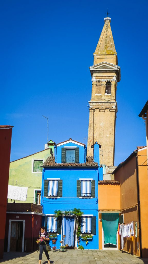This is a photo of the leaning bell tower of San Martino church in Burano, Veneto, Italy. Venice islands, the perfect Venice day trip.