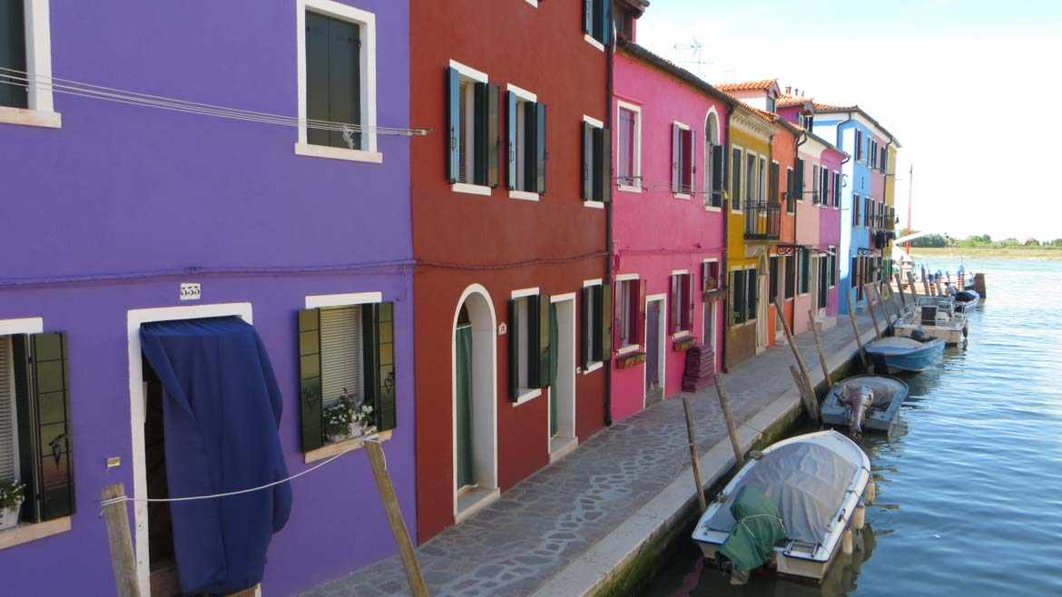 This photo shows a row of vividly coloured houses on the island of Burano near Venice, Italy. Venice islands, the perfect Venice day trip.