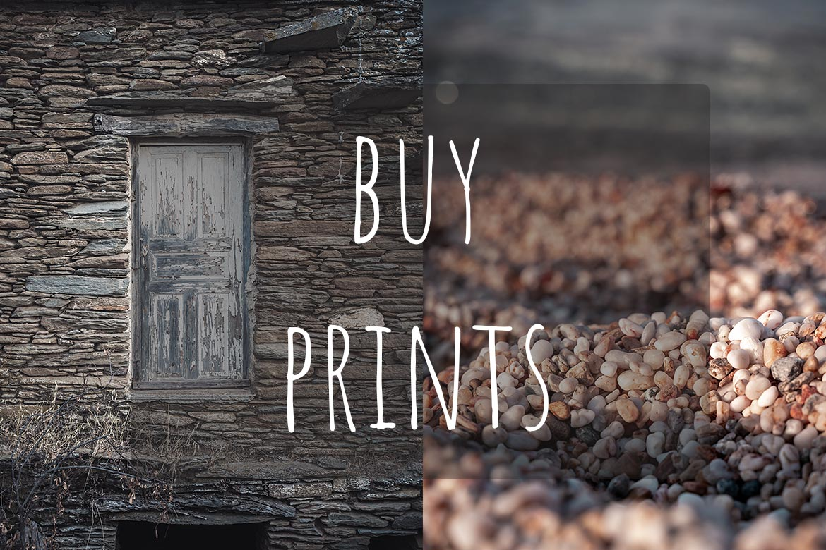 This image shows two photos side by side. From left to right, the first photo shows a wooden door of a traditional house and the second one shows a close-up of pebbles on a beach. Both photos are taken in Andros Greece. This image is the cover of our buy prints section.