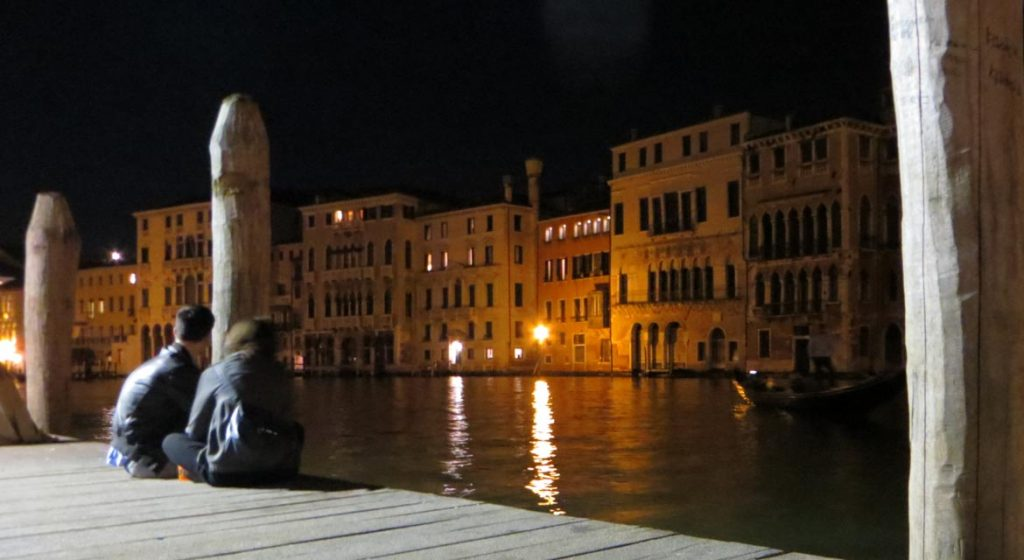 This is a photo of the wooden platform on the Grand Canal near Campo Erberia in Venice, Italy, where locals enjoy their drinks in the evening. What to do in Venice: our complete guide to La Serenissima.
