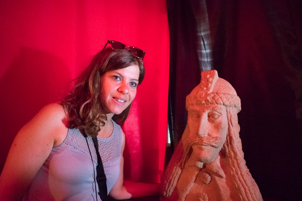 This is a photo of Katerina posing next to Dracula in Casa Vlad. What to do in Sighisoara Romania in 24 hours.