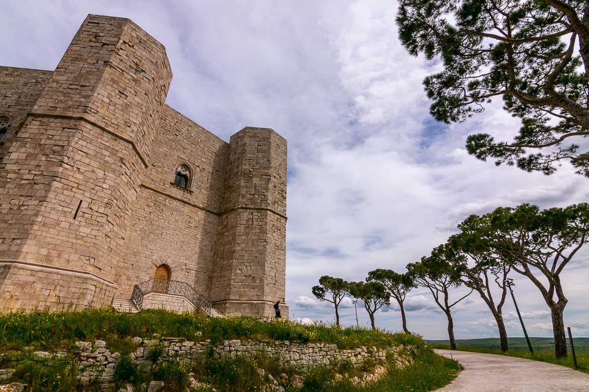This photo shows the exterior of Castel Del Monte. There are flower beds and trees surrounding the castle.