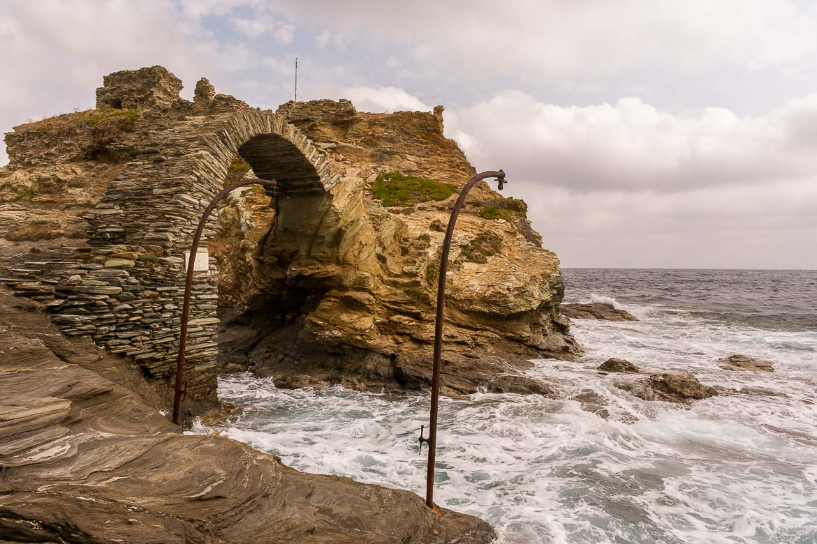 Huge waves crashing on the remains of the Lower Castle of Andros. 13 unique things to do in Andros Greece and full Andros Guide.