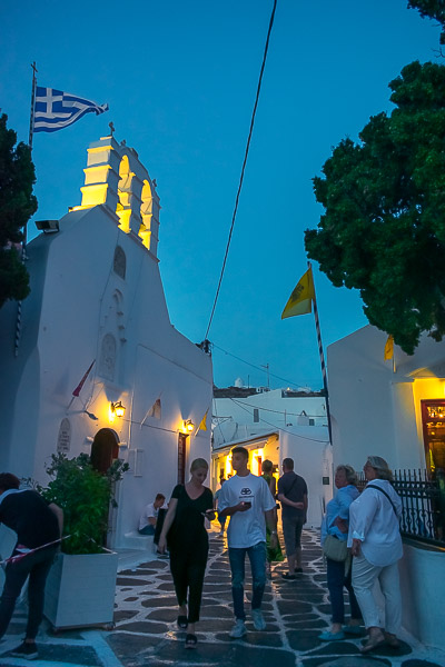 This is an image of a whitewashed street in Chora Mykonos. It's not yet completely dark and the sky has a wonderful blue colour. There is a beautifully lit church and people walking along the street.