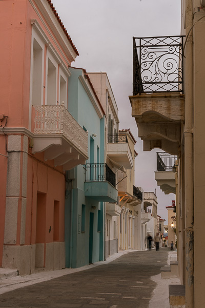 The main street in Chora Andros lined with pastel-coloured neoclassical mansions.
