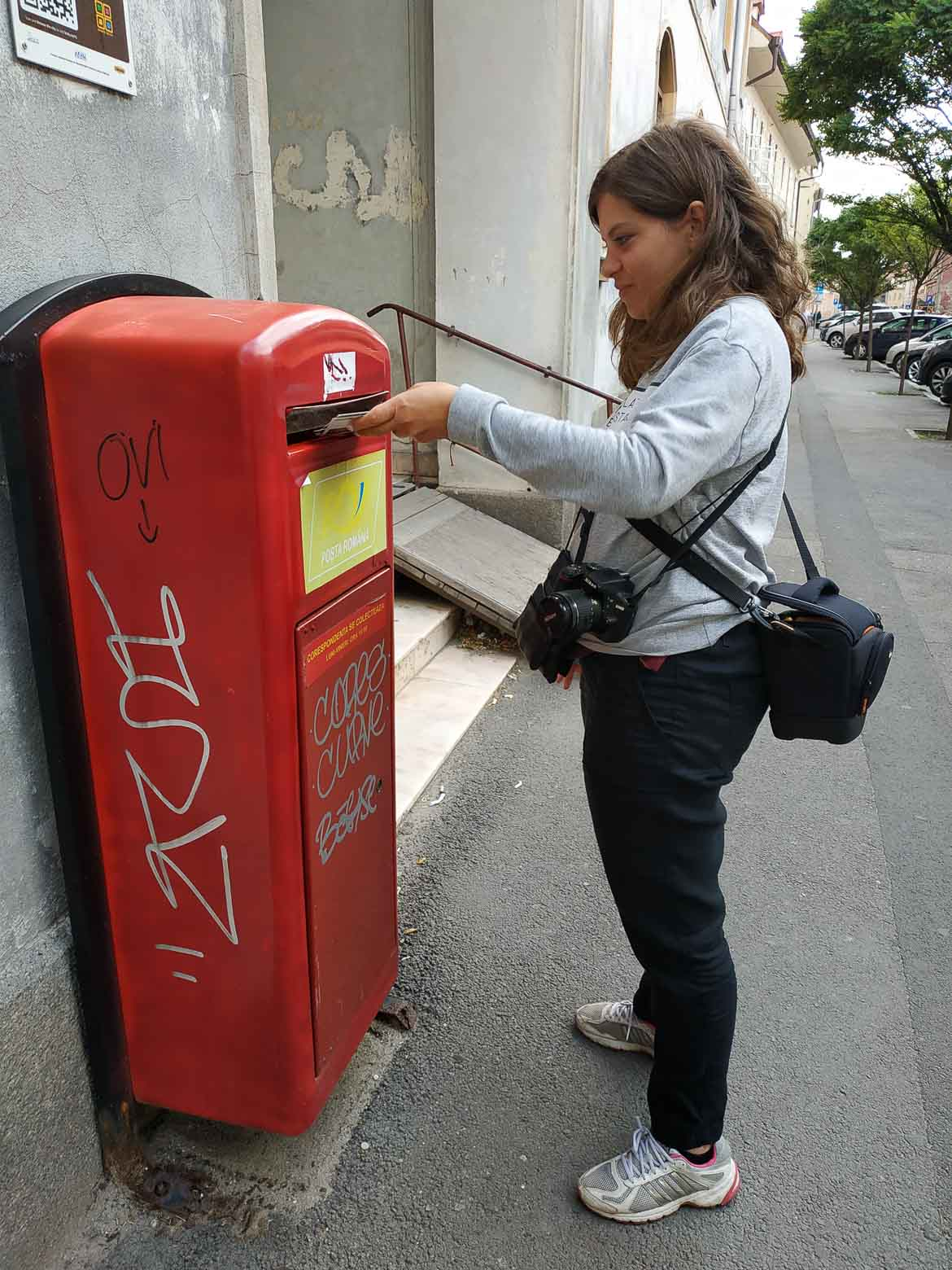 This is a photo showing Katerina mailing postcards from Sibiu, Transylvania, Romania. We always stay in contact with our loved ones while travelling. It's all trip to me travel blog.