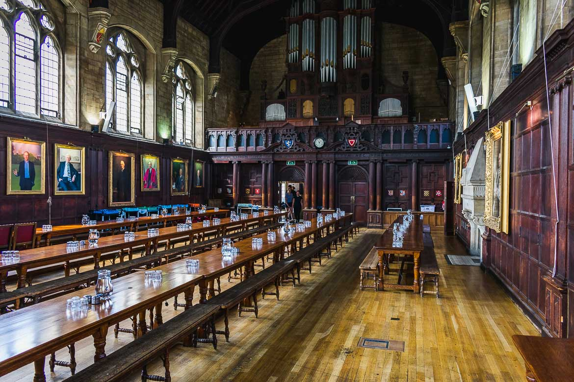 This photo shows the Dining Hall in Balliol College, University of Oxford, England. There are empty long wooden tables with glasses on them. The hall is empty and peaceful.