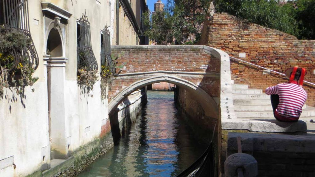 This photo shows a peaceful canal in the Dorsoduro district in Venice, Italy, with a gondolier sitting idly beside it. What to do in Venice: our complete guide to La Serenissima.