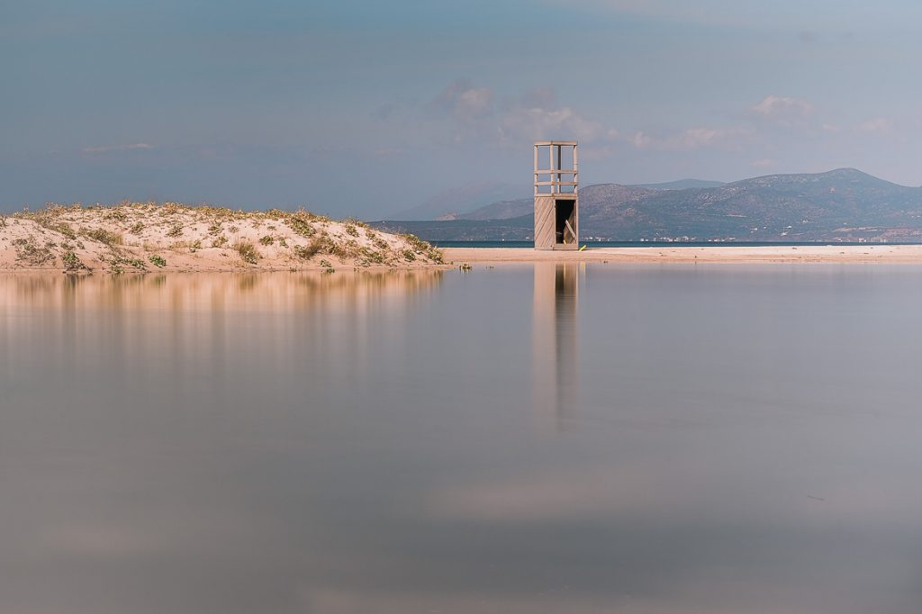 This is a photo of a pond that's forming at Ta Nisia Tis Panagias Beach in Elafonisos Greece outside summer months. There's an old wooden lifeguard tower reflecting on the water.