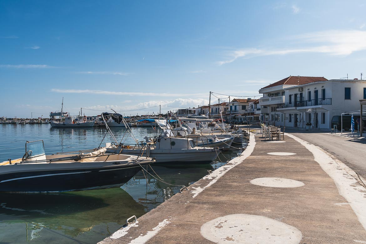 This is an image of the promenade in Elafonisos Town. There are many fishing boats anchored along the seafront.