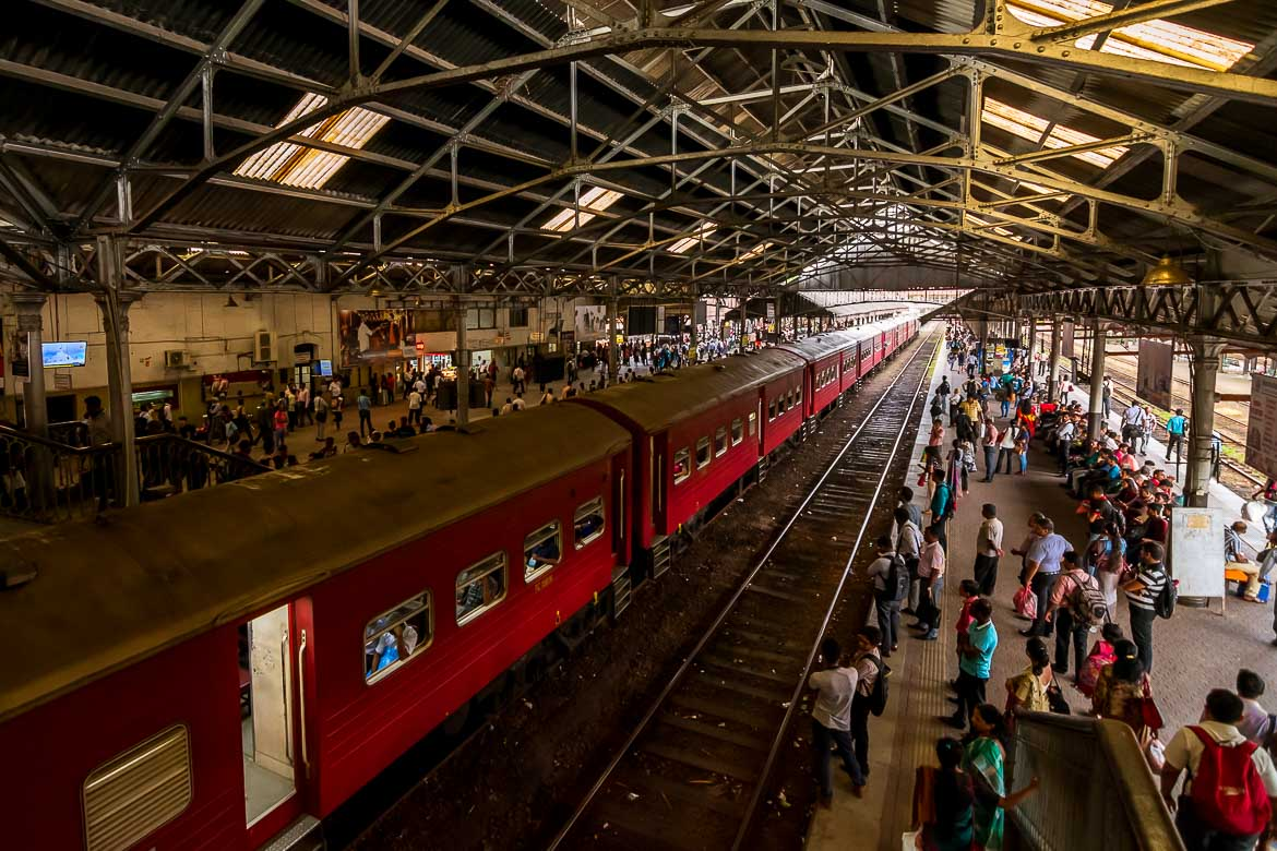 This photo was shot inside the Fort Railway Station. There is a red old fashioned train and many people waiting at the platform.
