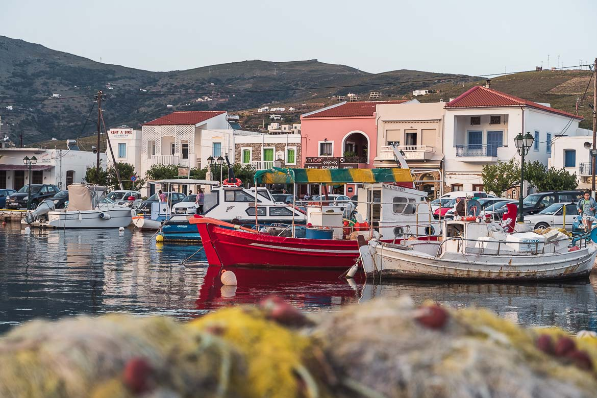 This is a shot of Gavrio Port in Andros. It's the part of the port where small fishing boats are anchored. There's a line of traditional buildings in the background.