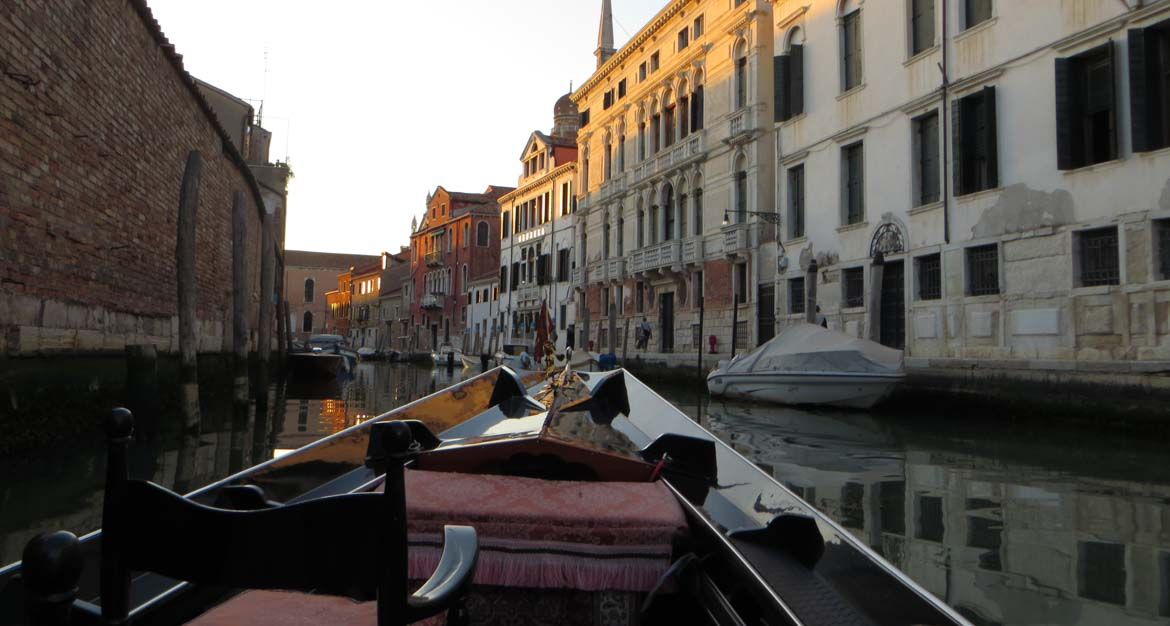 This picture is taken from a private gondola ride and it shows a peaceful canal with beautiful buildings on both of its banks. Top things to do in Venice Italy.