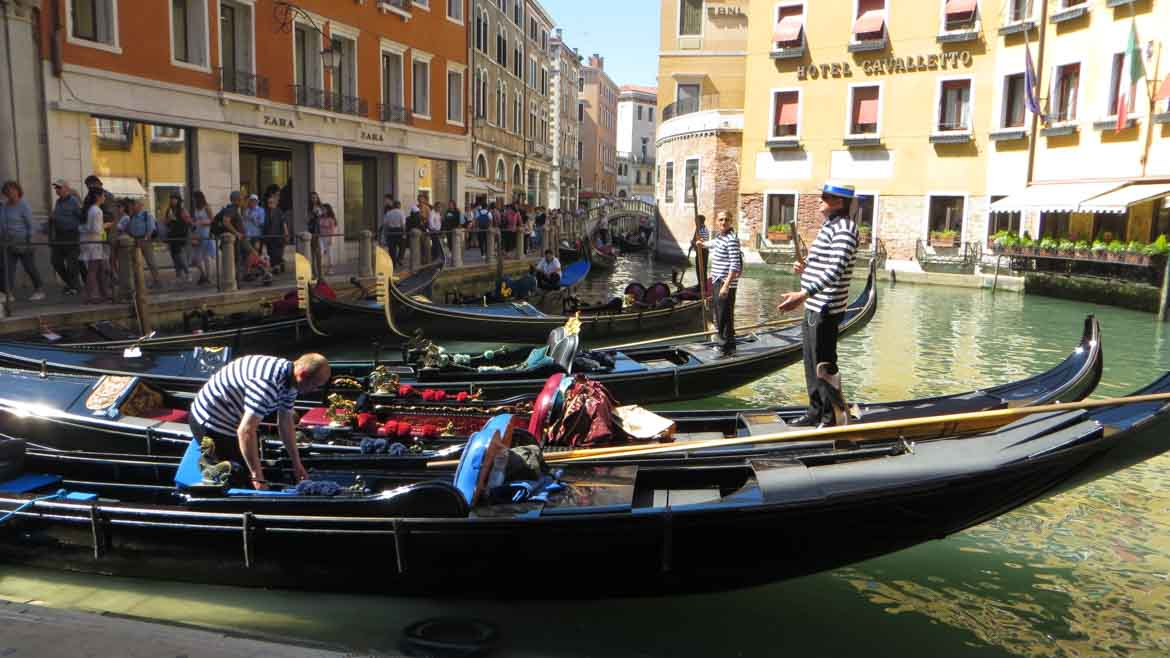 This picture shows gondolas waiting in line to take visitors for a private gondola ride on the canals of Venice, Italy. Top things to do in Venice. What to do in Venice.