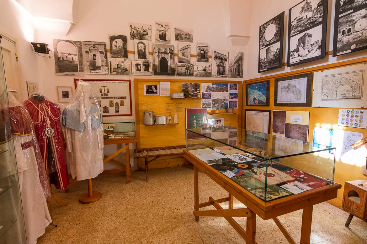 This photo shows various displays inside the folk museum in Calimera. There are three traditional costumes as well as old LPs, maps and black and white photos.