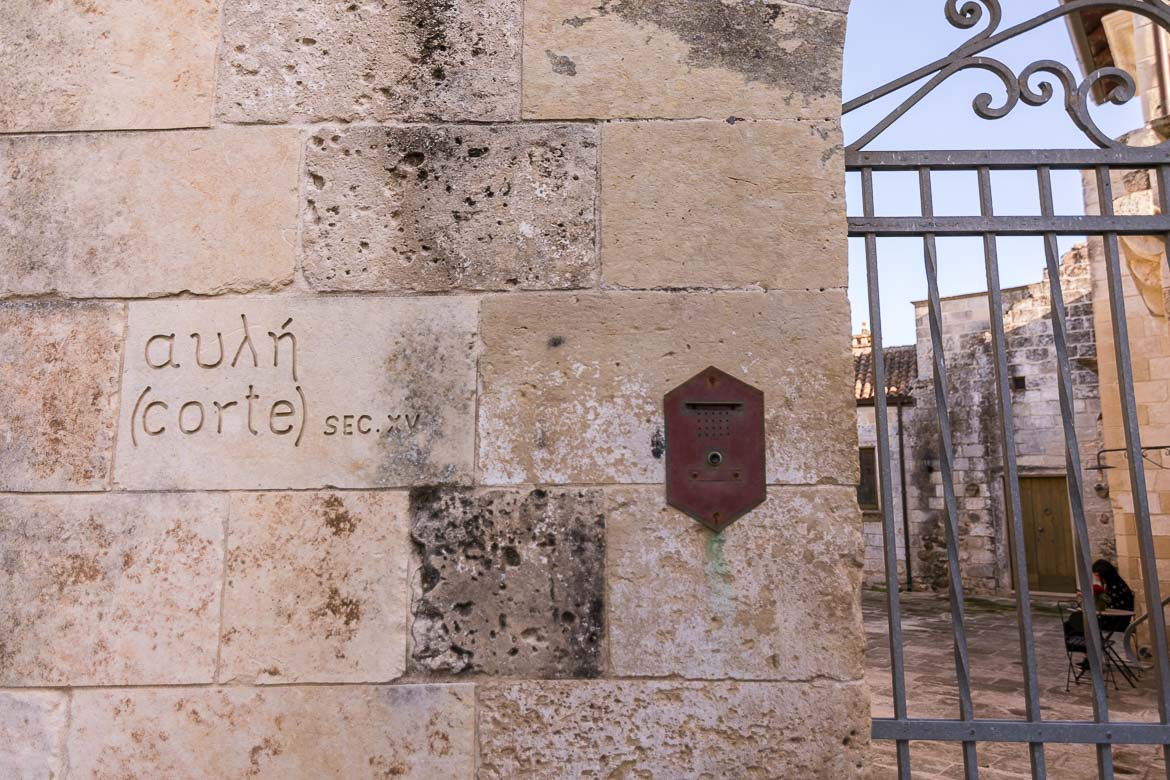 This is a close up of a wall sign that reads αυλή and corte.