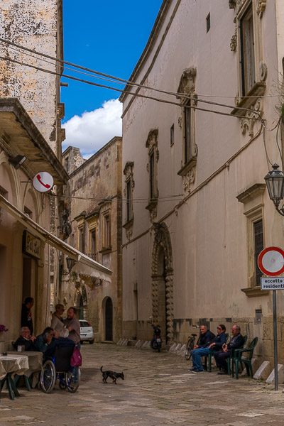 This image shows a quaint street in Corigliano d'Otranto. People are sitting on chairs on both sides of the street chatting.