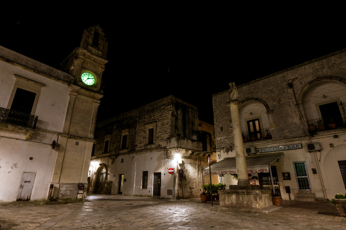 This is a night shot of Corigliano d'Otranto. There is a clock tower and a closed Italian bar.