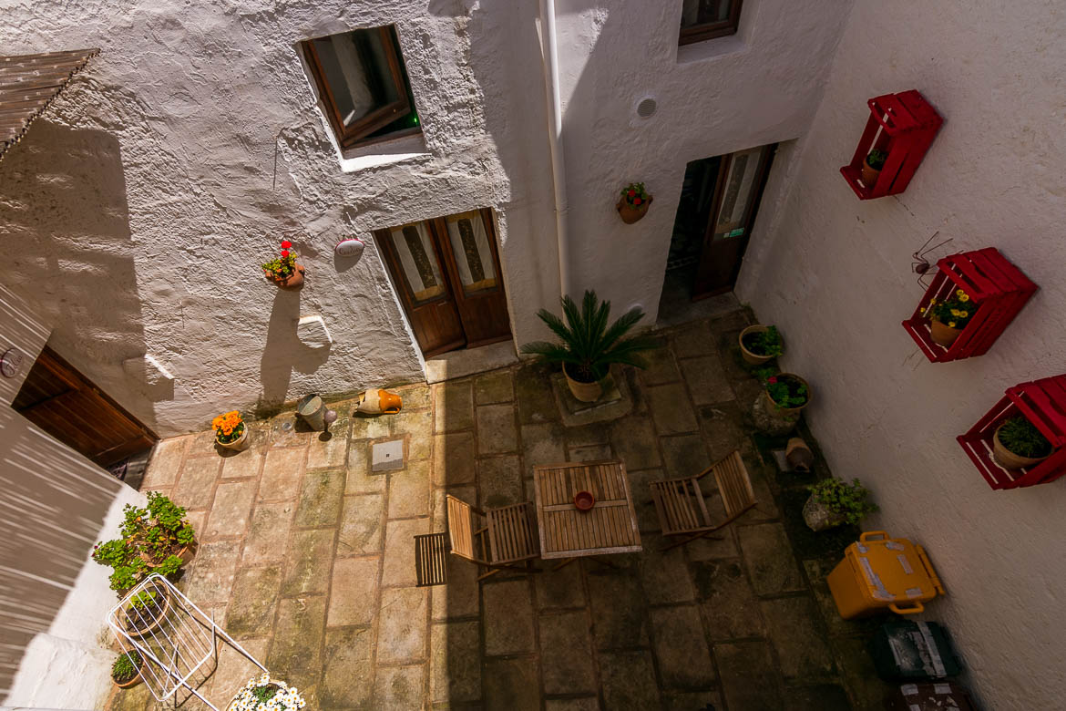 This photo was shot from above and shows the casa a corte. This architecture style is typical of this area in Italy. We can see two doors opening to the same courtyard. There is a table, chairs and flower pots there.