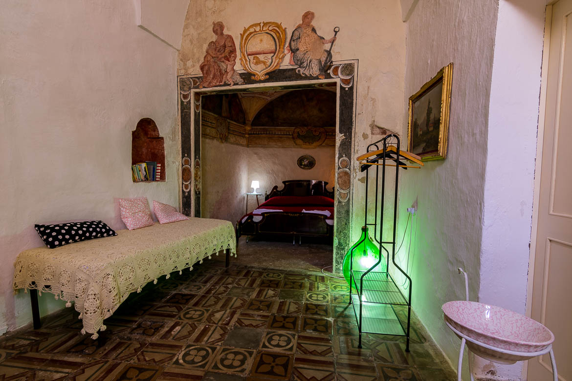 This room shows the interior of a room at Corte Candelora B&B. The furniture is old-fashioned and there is a green lamp. The floor has the same tiles it used to have since its construction. On the walls, there are painted frescoes with religious themes.