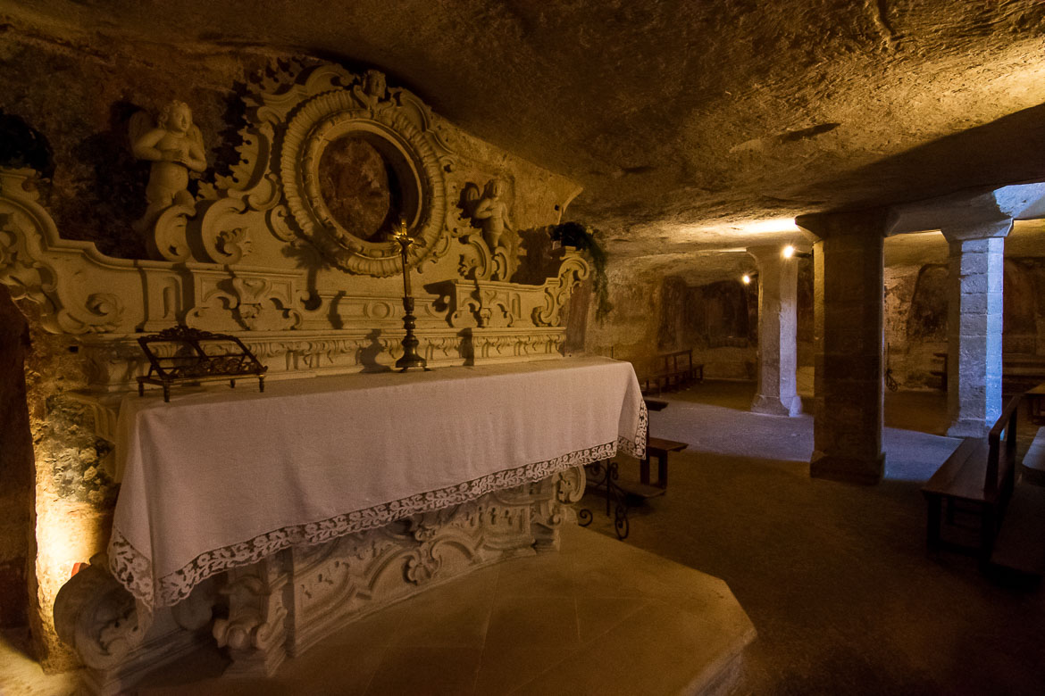 This photo was shot inside the Crypt of Santa Cristina. There is an altar with a precious Virgin Mary icon above it. In the background, the frescoes on the walls are barely visible.