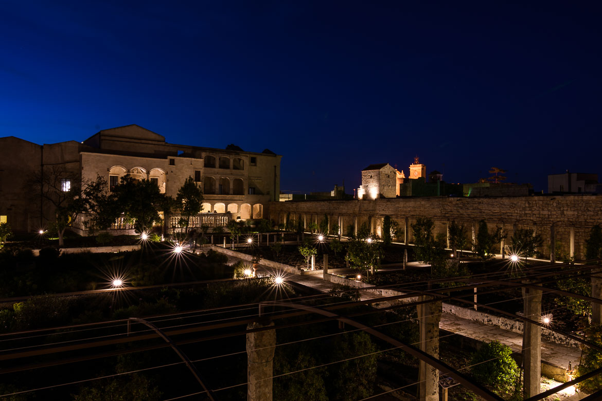 This photo was taken inside the garden of Palazzo Marchesale in the evening. The garden and the castle are dimly lit.