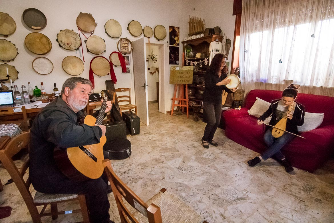 This picture shows Salvatore playing the guitar, Mariella playing the tambourine and singing and Letizia playing the lyre inside Melpignano Cultural Centre.