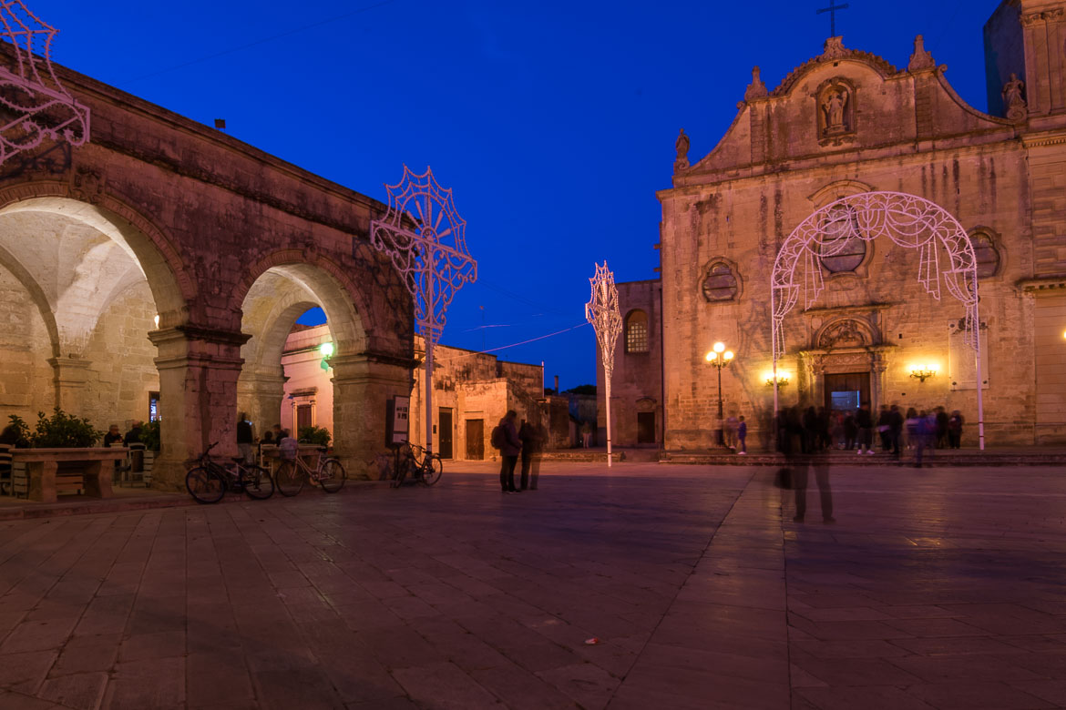 This is a photo of Piazza san Giorgio in the evening. The church and the market building are lit and the sky is light blue.