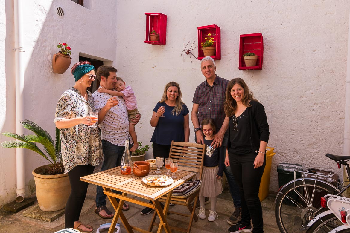 This photo shows Maria, Katerina and a party of 4 more people raising their aperitivo glasses to toast. The setting is the courtyard of Corte Candelora B&B. One of the moments we cherish about our Grecia Salentina trip.