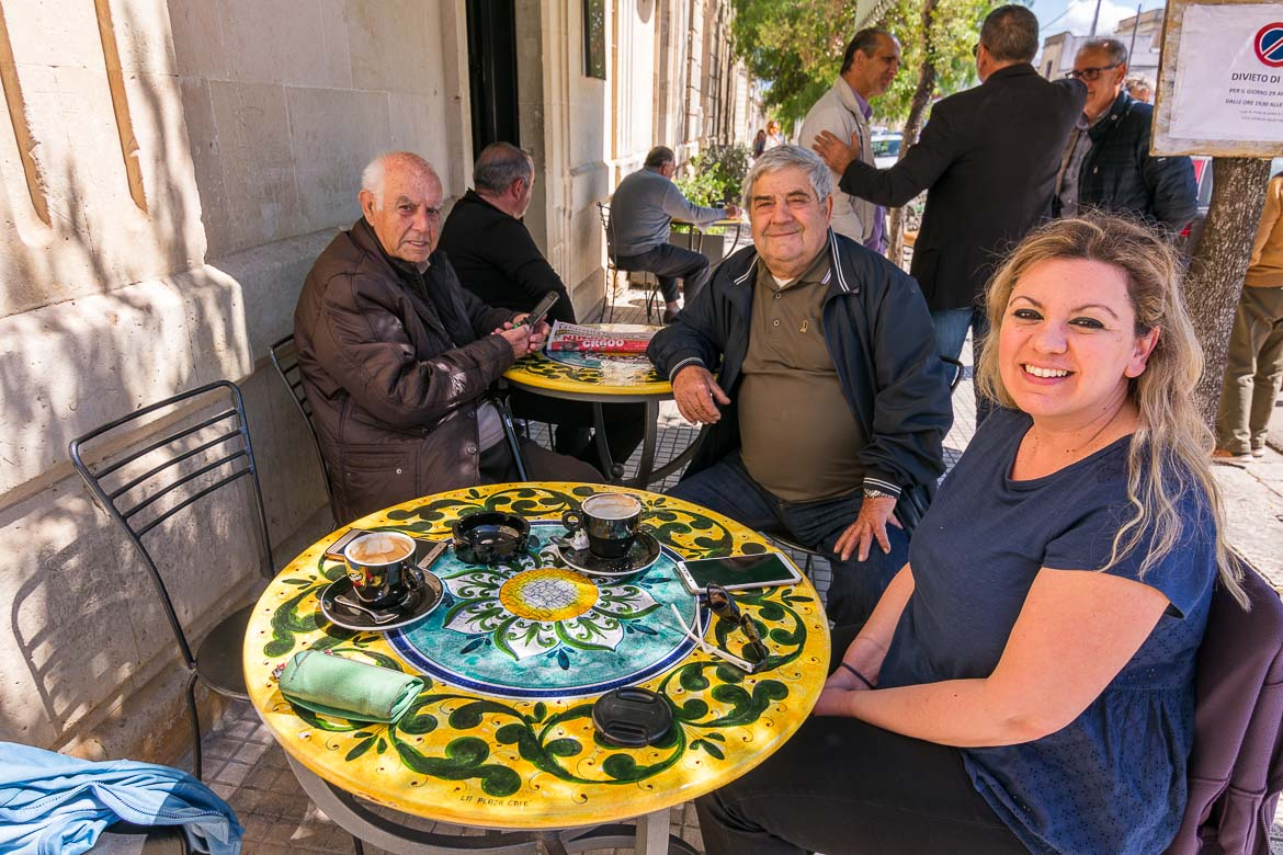 This photo shows Maria sitting at an outside cafe with Mimmo and Uccio on a sunny day.