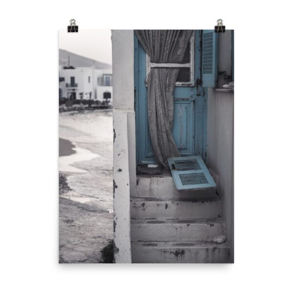 This image shows a blue door with an old curtain. In the background, the sea and Naoussa Paros. This is our Greek Island Print, part of our Greece prints collection, available for sale on our Print store!