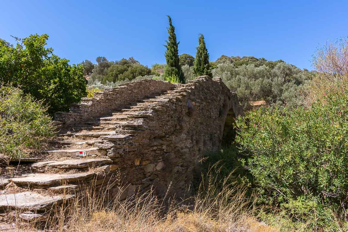 This image shows Stichiomeni (Haunted) Bridge, a traditional bridge made of stone amidst olive trees and cypresses.