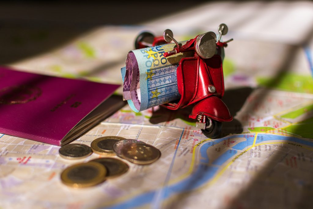This photo shows a miniature vespa with money on it. There is also a map, a passpot and some coins. We've chosen this photo to be the featured image for our article: How to afford to travel often: Top 27 tips to save money.