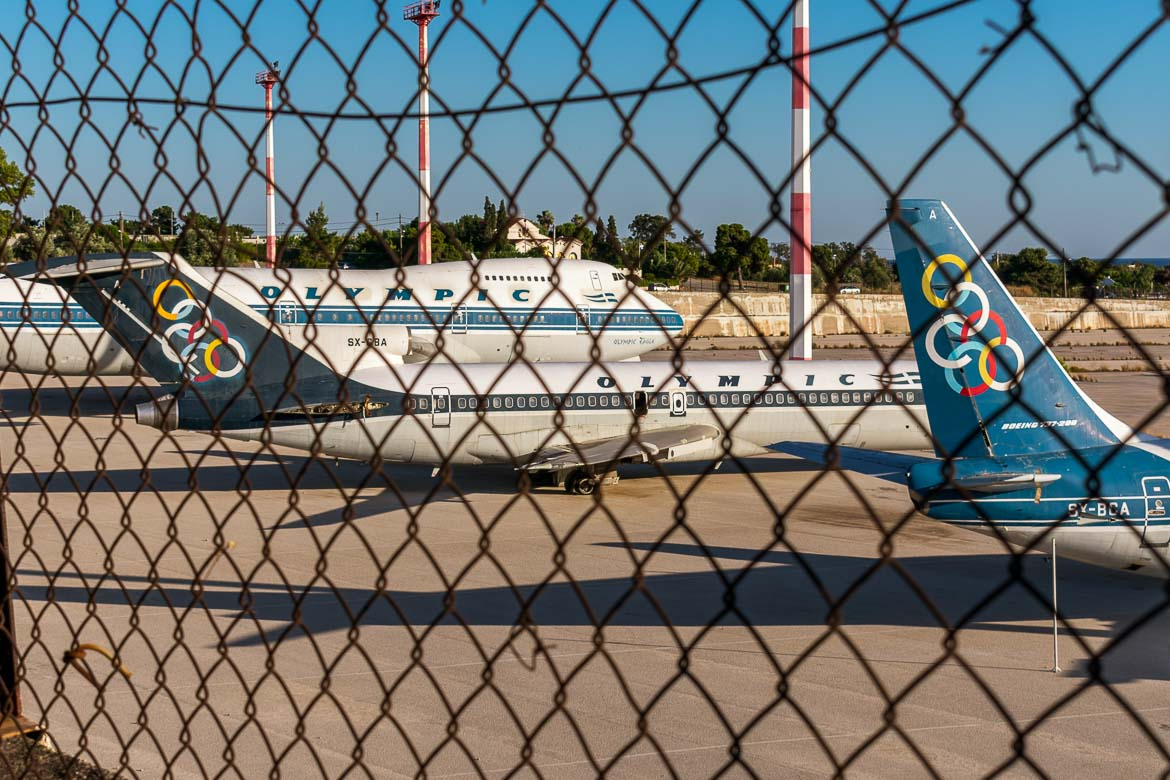 This is a photo of some old Olympic Airways planes at the old airport in Athens Greece as seen from behind the fence.