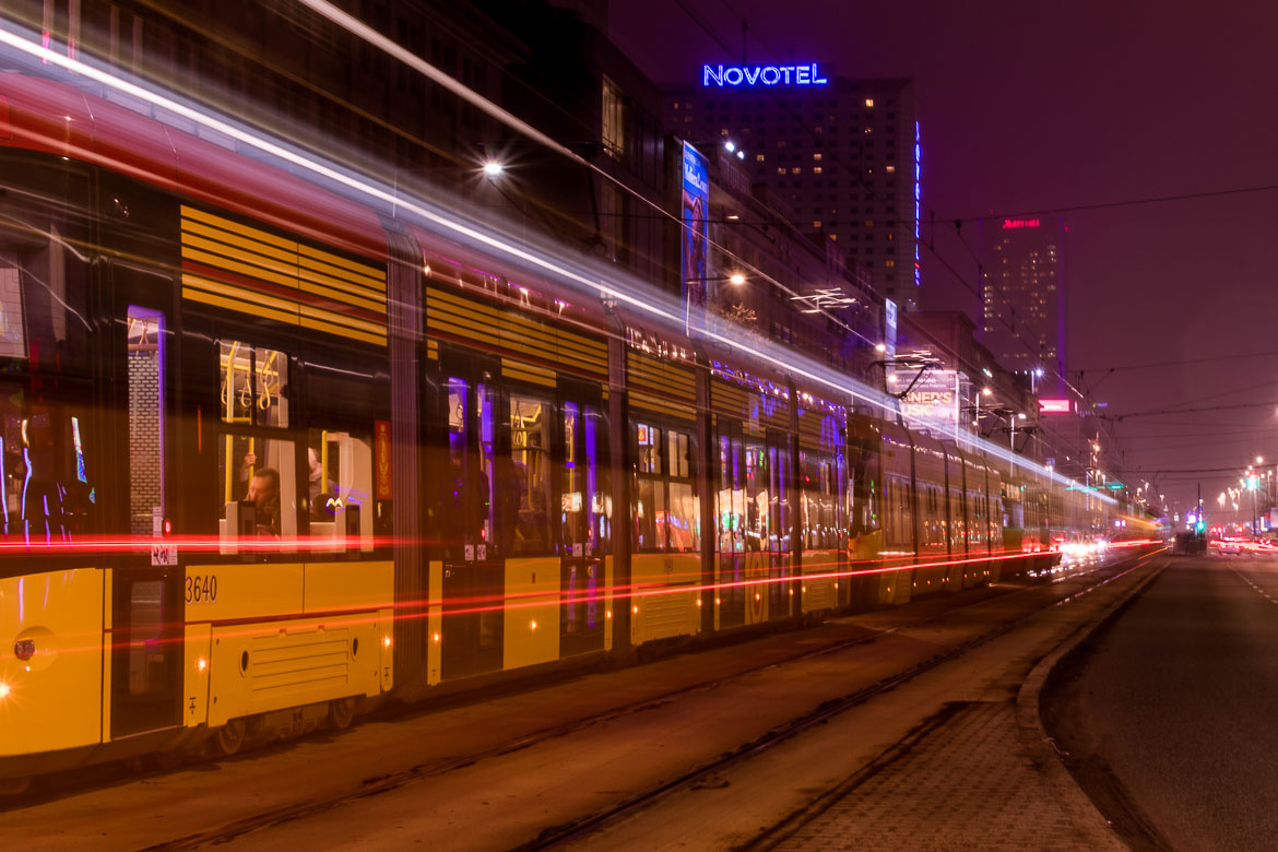 This is a long exposure night shot of a tram in Warsaw Poland.