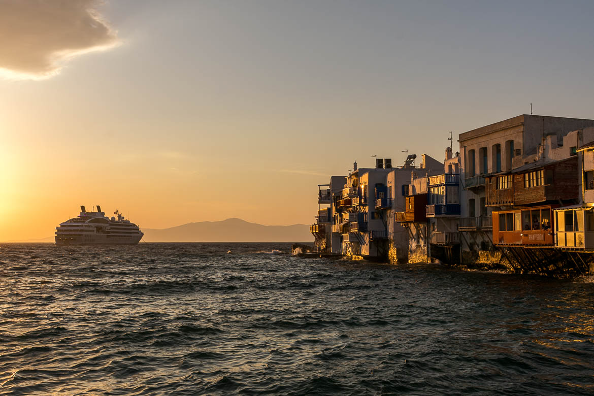 This is a photo of Little Venice in Mykonos at sunset. The sky is orange and there is a huge cruise ship near the shore.