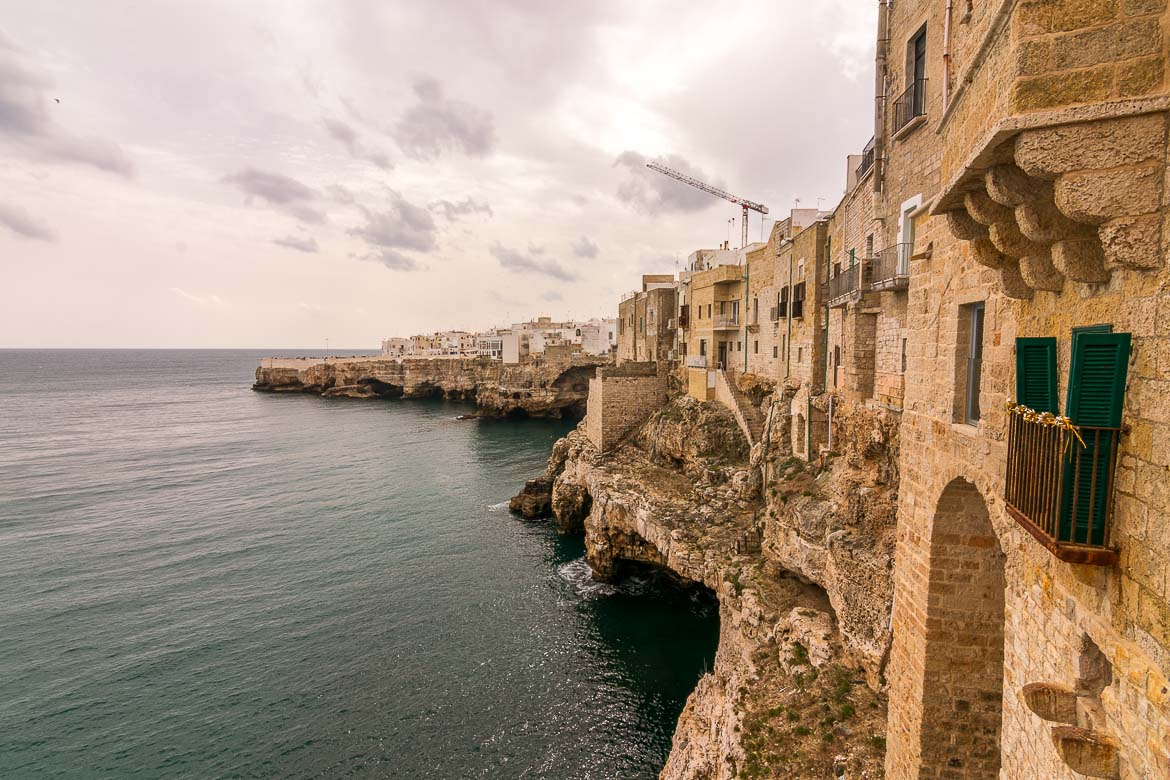 This photo shows the old fashioned buildings which seem as if they're hanging above the sea in Polignano a Mare, Puglia, Italy.