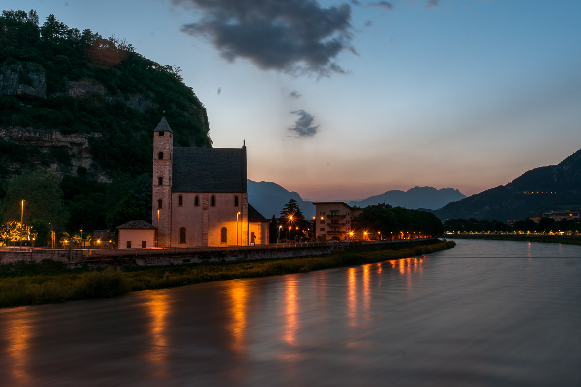This photo shows St Apollinare Church dimly lit at sunset. The church is built right next to the tranquil waters of Adige River so the views are amazing.