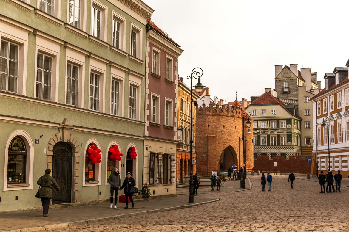 This photo shows Warsaw old town. In the background the Barbican. In the foreground, a series of pastel coloured buildings line a quaint cobblestone street.