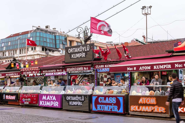 Lines of kumpir stalls at Ortaköy. Kumpir is a fantastic Istanbul street food. Istanbul food guide: Sugar, spice and love.