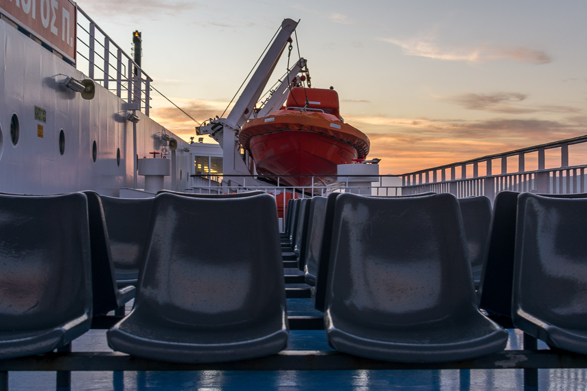 This image was shot inside a Fast Ferries ferry. It is a shot showing empty seats on the deck and a beautiful sunset in the background.