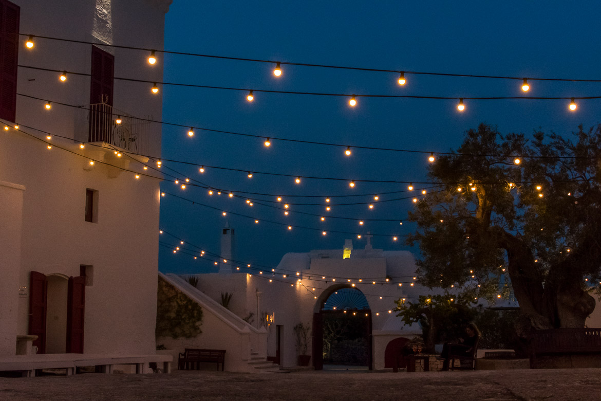 This image shows the courtyard at Masseria Torre Coccaro in Puglia, Italy in the evening. There are lines of lights hanging above.
