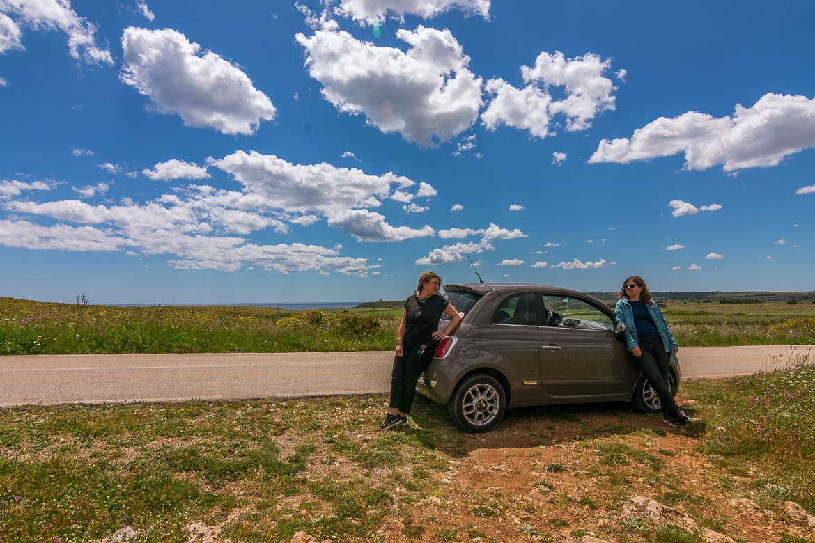 This photo shows Maria and Katerina posing in front of their Fiat 500 at the side of a road somewhere in Puglia. There is a magnificent bright sky with white clouds and there is green landscape all around and far in the distance.