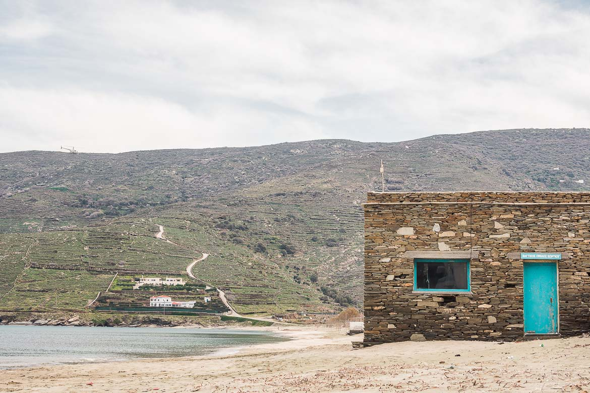 This image shows a stone-built building built right on the sand at Korthi Bay. It's bright turquoise door comes in striking contrast with the cloudy day.