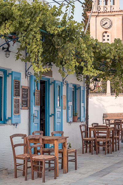 This is the facade of one of the most beautiful cafes in Lefkes, to Kafeneio tis Marigos. The doors and shutters are painted light blue and there are brown tables and chairs outside, right underneath a lush vine.