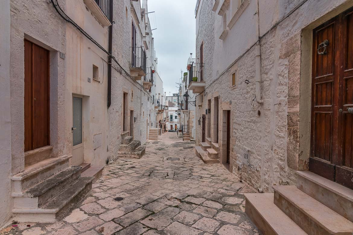 This image shows a quaint street in Locorotondo Old Town. It's a narrow alley with beautiful white buildings on both sides. There are no vehicles nor people.