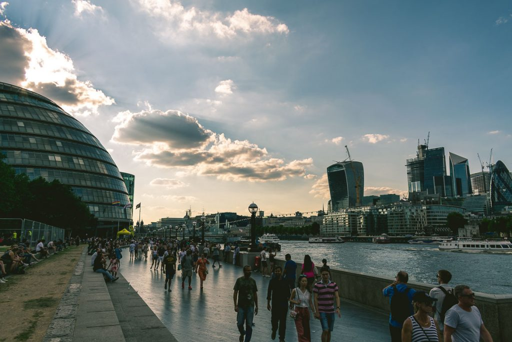This photo shows the Thames South Bank at sunset. People walking in front of the City Hall in London, England. This is our favourite South Bank walk.