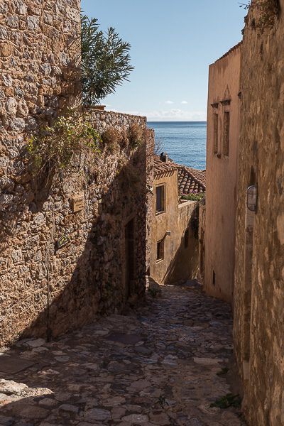 This photo shows a beautiful cobbled alley in Monemvasia Castle. In the background, the sea is visible.