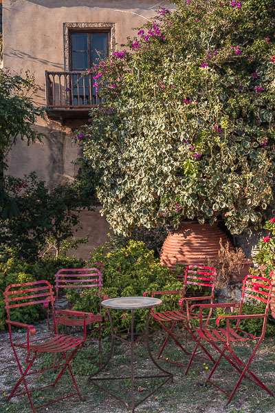 This photo shpws a set of four red chairs around a small table in front of a traditional house in Monemvasia Castle.