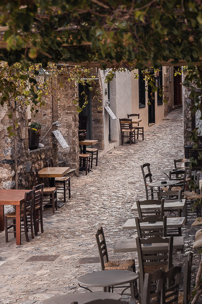 This photo shows the main street (Kalderimi) inside Monemvasia Castle. There are table and chairs lining both sides and vines hanging above.